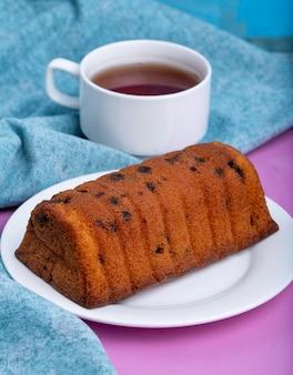 Vista lateral do bolo com passas em um prato branco e uma xícara de chá preto em roxo e azul