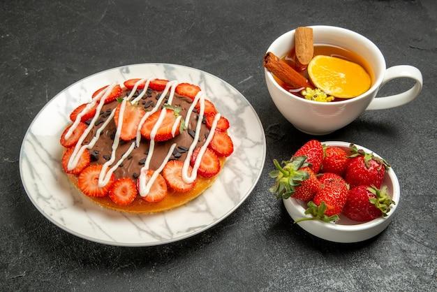 Vista lateral do bolo com uma xícara de chá de bolo com morangos e chocolate ao lado da tigela de morangos e a xícara de chá com limão e canela em pau na mesa preta