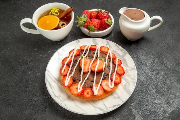 Vista lateral do bolo com uma xícara de chá de bolo com morangos e chocolate ao lado da tigela de morangos e creme de chocolate e a xícara de chá com limão e canela em pau na mesa preta