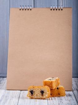 Vista lateral do bolo de biscoito com chocolate no fundo do caderno