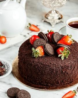 Vista lateral do bolo de chocolate decorado com morangos e biscoitos em cima da mesa