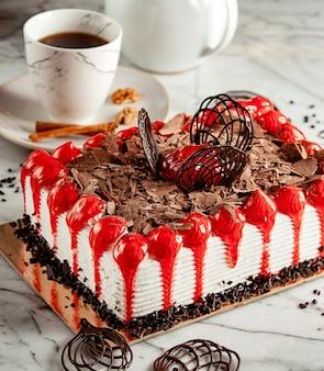 Vista lateral do bolo de frutas coberto com flocos de chocolate em cima da mesa, servida com chá