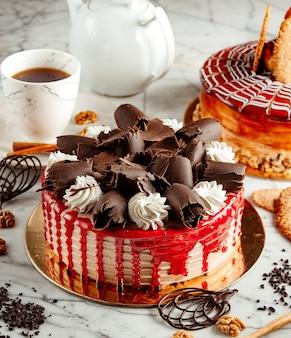 Vista lateral do bolo de frutas coberto com raspas de chocolate e chantilly em cima da mesa, servida com chá
