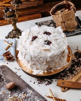 Vista lateral do bolo decorado com pedaços de chocolate brancos em cima da mesa