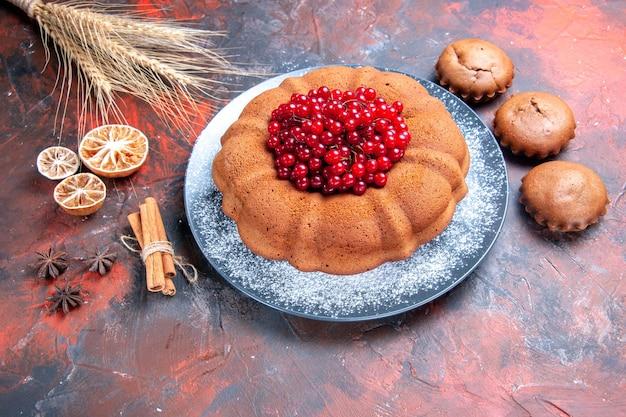 Vista lateral do bolo e cupcakes um bolo com frutas cupcakes anis estrelado canela paus de limão