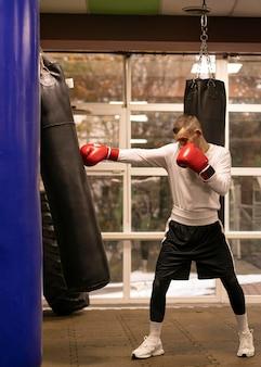 Vista lateral do boxeador praticando com o saco de pancadas próximo ao ringue