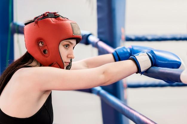 Vista lateral do boxer feminino ao lado do anel