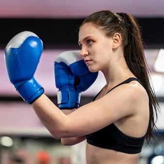 Vista lateral do boxer feminino com luvas de proteção