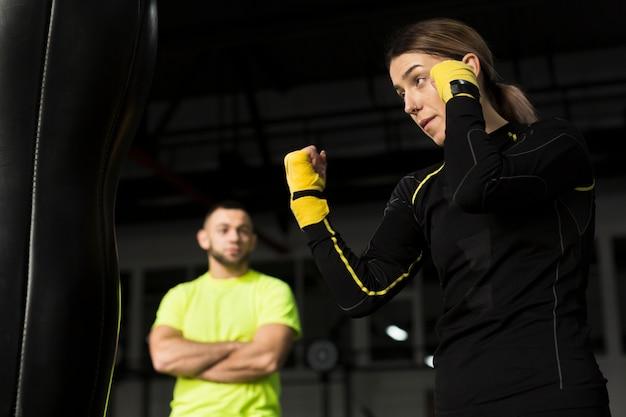 Vista lateral do boxer feminino praticando com treinador desfocado assistindo