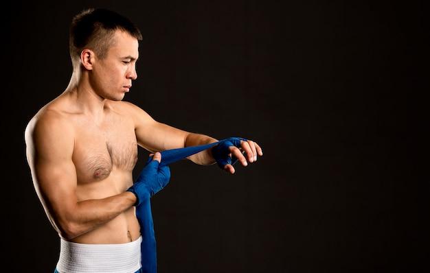 Vista lateral do boxer masculino, colocando proteção para as mãos, com espaço de cópia