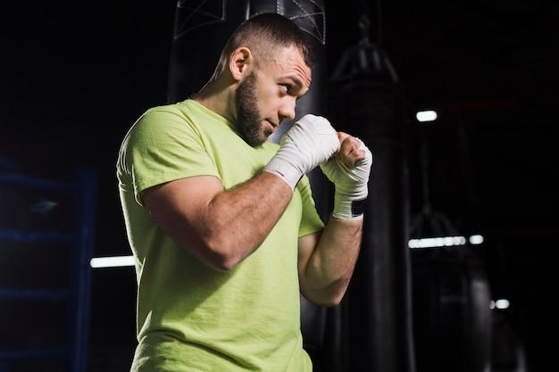 Vista lateral do boxer masculino em camiseta praticando no ginásio