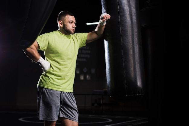 Vista lateral do boxer masculino em t-shirt com saco de pancadas
