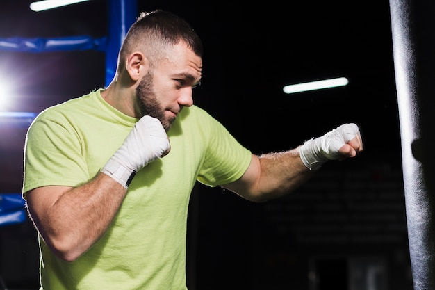 Vista lateral do boxer masculino em t-shirt trowing socos no saco pesado