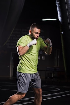 Vista lateral do boxer masculino vestindo camiseta e shorts praticando com saco de pancadas