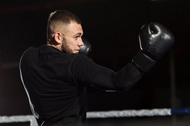 Vista lateral do boxer posando em luvas de proteção