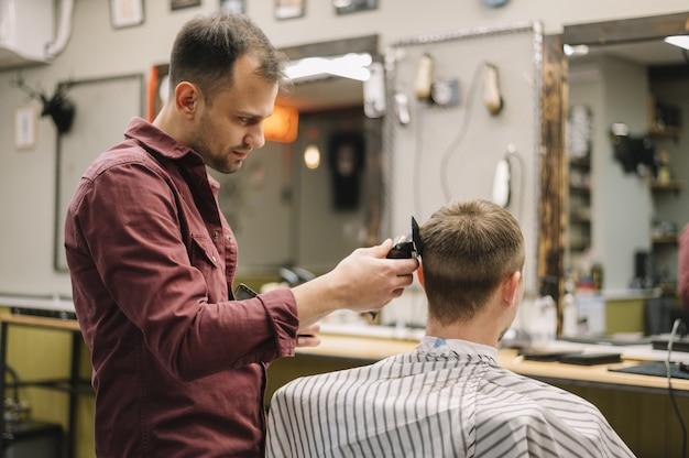 Vista lateral do cabeleireiro dando um corte de cabelo