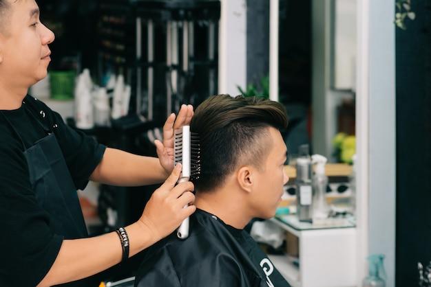 Vista lateral do cabeleireiro, pentear cabelo para cliente masculino