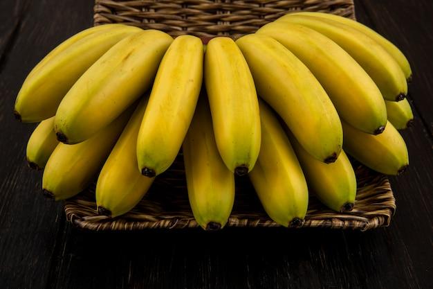 Vista lateral do cacho de bananas em uma cesta de vime no escuro
