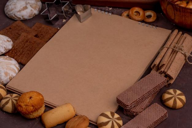 Vista lateral do caderno com diferentes cookies em torno de muffins de gengibre crocante varas waffles de chocolate no escuro