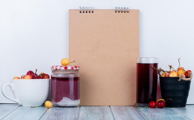 Vista lateral do caderno e cerejas frescas maduras mais chuvosas em um copo de balde e tigela de suco e geléia de cereja em uma jarra de vidro no rústico