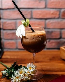 Vista lateral do café coquetel com licor e creme em uma mesa de madeira