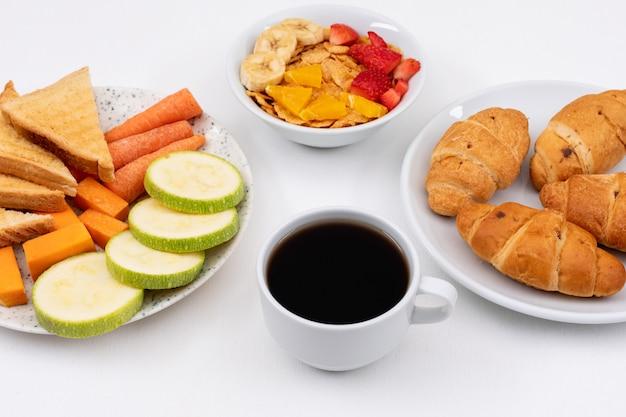 Vista lateral do café da manhã com croissants, flocos de milho e café na superfície branca horizontal
