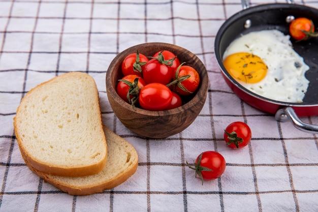 Vista lateral do café da manhã com panela de ovo frito e tigela de tomate com fatias de pão na superfície do pano xadrez