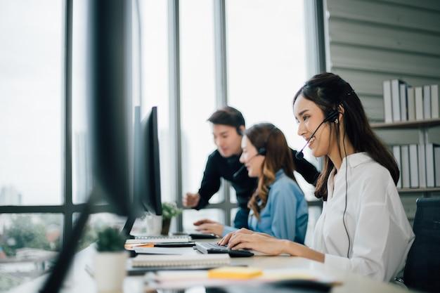 Vista lateral do call center da mulher com fones de ouvido usando computadores no escritório.