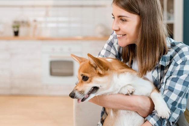 Vista lateral do cão sendo realizada por mulher