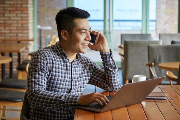Vista lateral do cara asiático, tendo uma ligação enquanto trabalhava no laptop