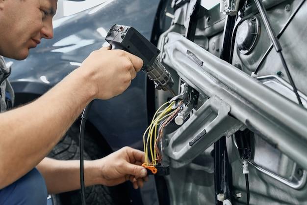 Vista lateral do carro elétrico usando ferro de solda para misturar o fio