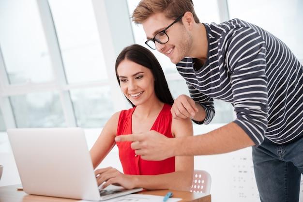 Vista lateral do casal à mesa com o laptop no escritório perto da janela. homem em pé perto da mulher e apontando para o computador tablet