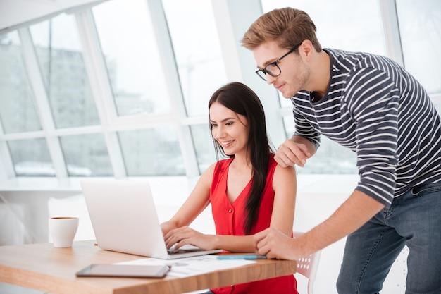 Vista lateral do casal à mesa com o laptop no escritório perto da janela. homem em pé perto de uma mulher sentada na cadeira
