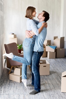 Vista lateral do casal abraçado em casa no dia da mudança
