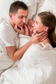 Vista lateral do casal abraçado na cama na cama e olhando um ao outro