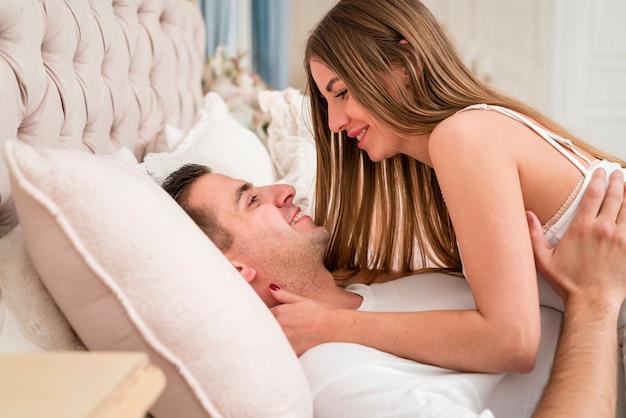 Vista lateral do casal abraçados na cama