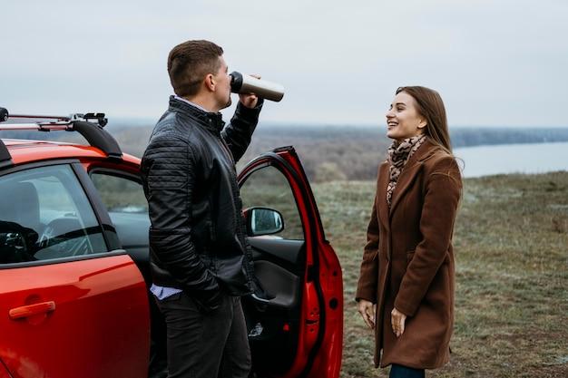 Vista lateral do casal ao lado do carro bebendo da garrafa térmica