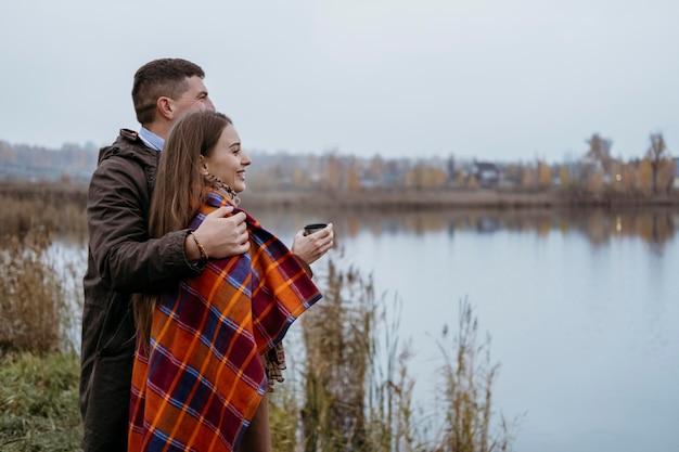 Vista lateral do casal com cobertor admirando a vista do lago