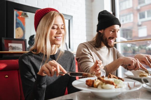 Vista lateral do casal comendo no café