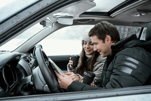 Vista lateral do casal consultando o mapa no carro durante uma viagem