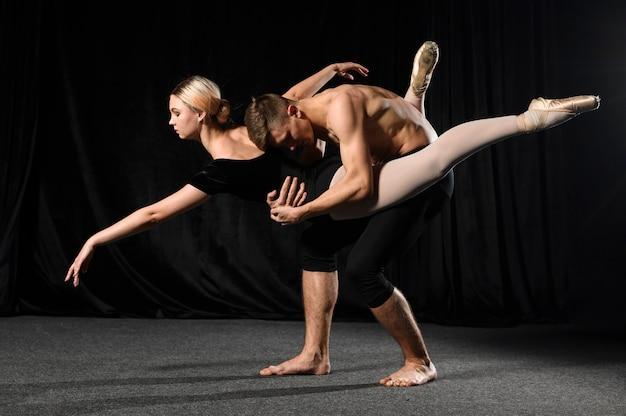 Vista lateral do casal de balé dançando no collant