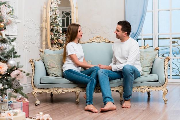 Vista lateral do casal de mãos dadas no sofá com árvore de natal