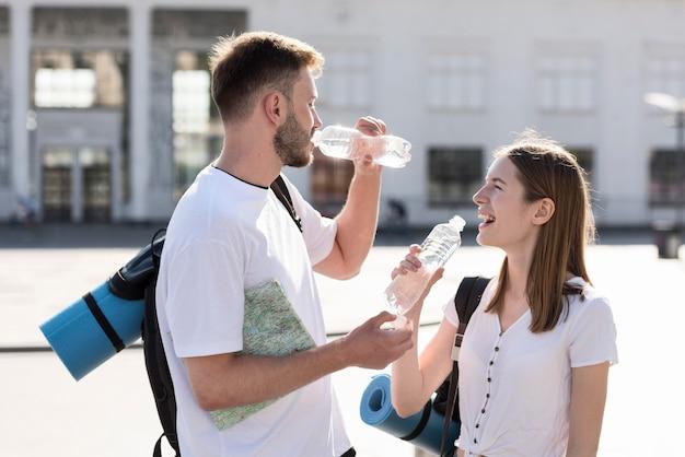 Vista lateral do casal de turistas, ficar hidratado ao ar livre