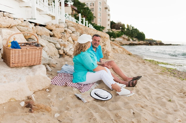 Vista lateral do casal de turistas mais velhos fazendo piquenique na praia