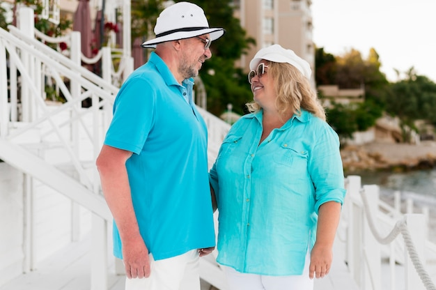 Vista lateral do casal de turistas mais velhos na praia