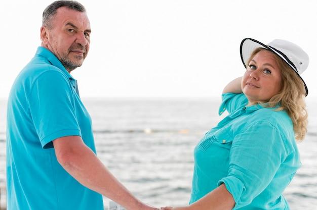 Vista lateral do casal de turistas mais velhos posando enquanto segura as mãos