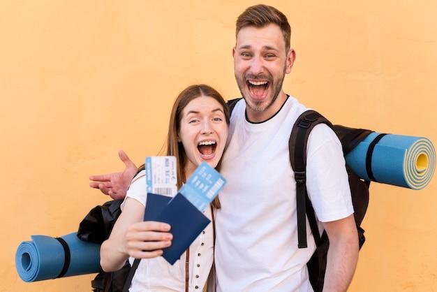 Vista lateral do casal de turistas sorridente com bilhetes de avião e passaportes