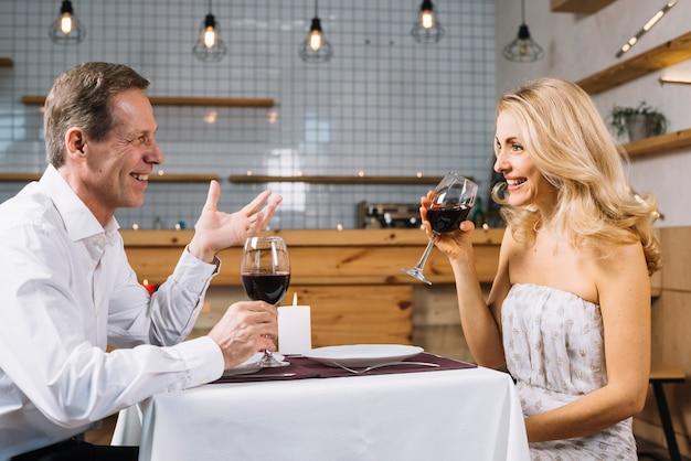 Vista lateral do casal durante um jantar romântico