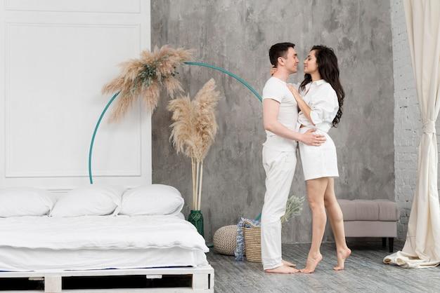 Vista lateral do casal em casa abraçado ao lado da cama