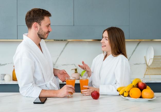 Vista lateral do casal em roupões de banho com copos de suco